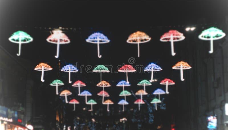 Straatparaplu met verschillende kleuren bij nacht stock afbeelding