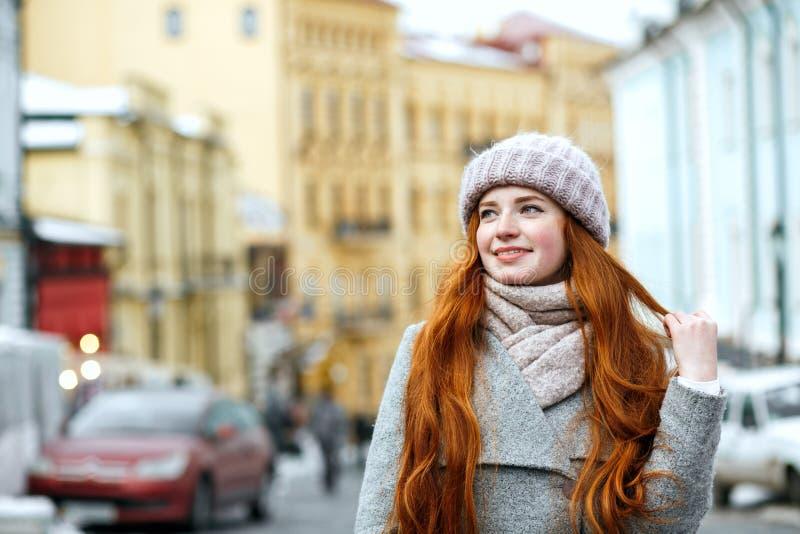 Straatportret van blij roodharigemeisje met lang haar die wa dragen stock foto's