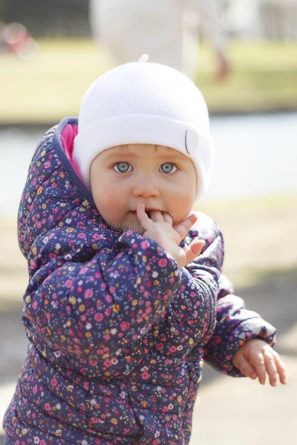 Straatportret van een klein meisje met blauwe ogen Een meisje bevindt zich op een achtergrond van stenen en kruiden royalty-vrije stock afbeelding