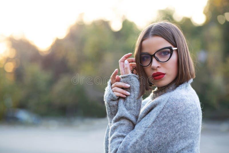 Straatportret van een mooi gelooid meisje die het gebreide sweater stellen op een straat dragen De ruimte van het exemplaar stock afbeeldingen