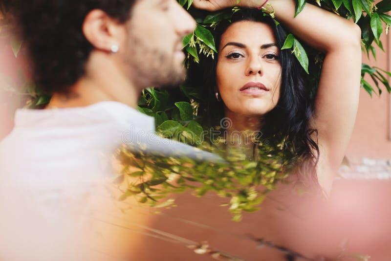 Straatportret van een vrouw op de achtergrond van groene bladeren In de voorgrond een vaag portret van een mens stock foto's