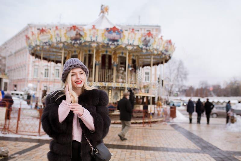 Straatportret van gelukkige blondevrouw die gebreide hoed dragen en fu stock afbeeldingen