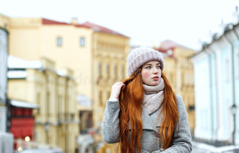 Straatportret van glorierijke roodharigevrouw met het lange haar dragen royalty-vrije stock afbeelding