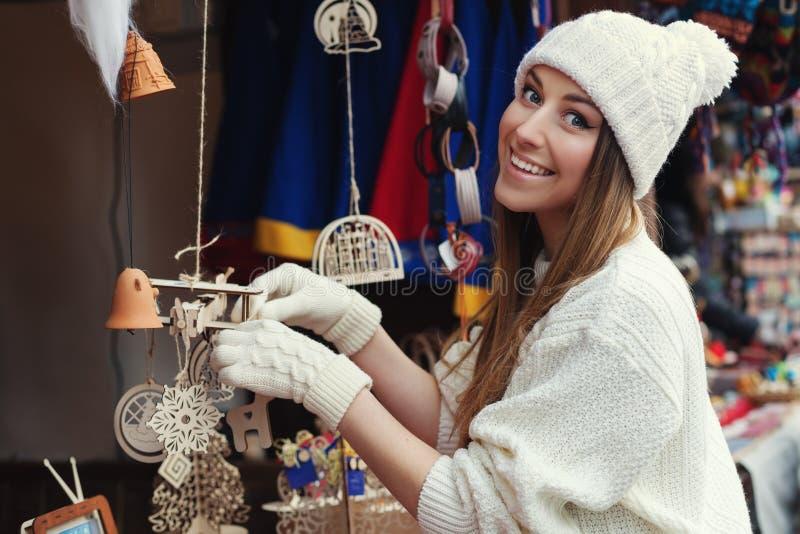 Straatportret van het glimlachen van mooie jonge vrouw het kopen decoratie op de feestelijke Kerstmismarkt Dame die schrijver uit royalty-vrije stock foto's