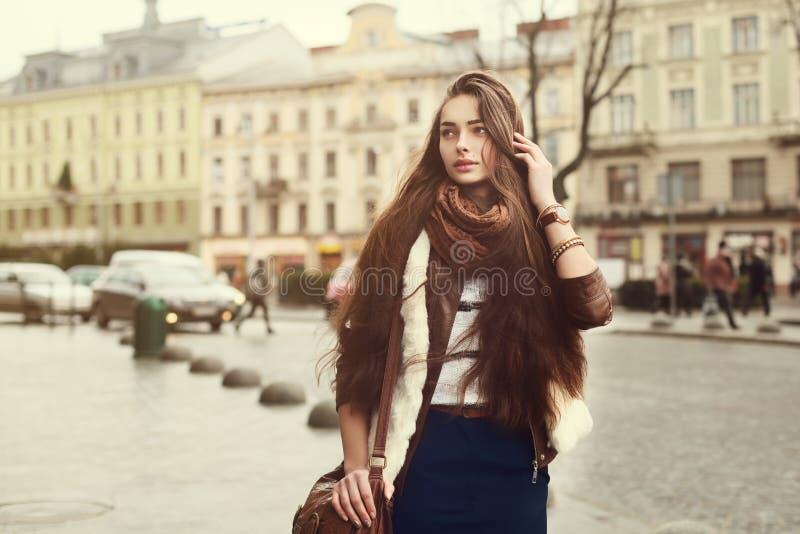 Straatportret van jonge mooie modieuze vrouw die modieuze kleren dragen die bij de oude stad lopen Modelleer het kijken stock fotografie