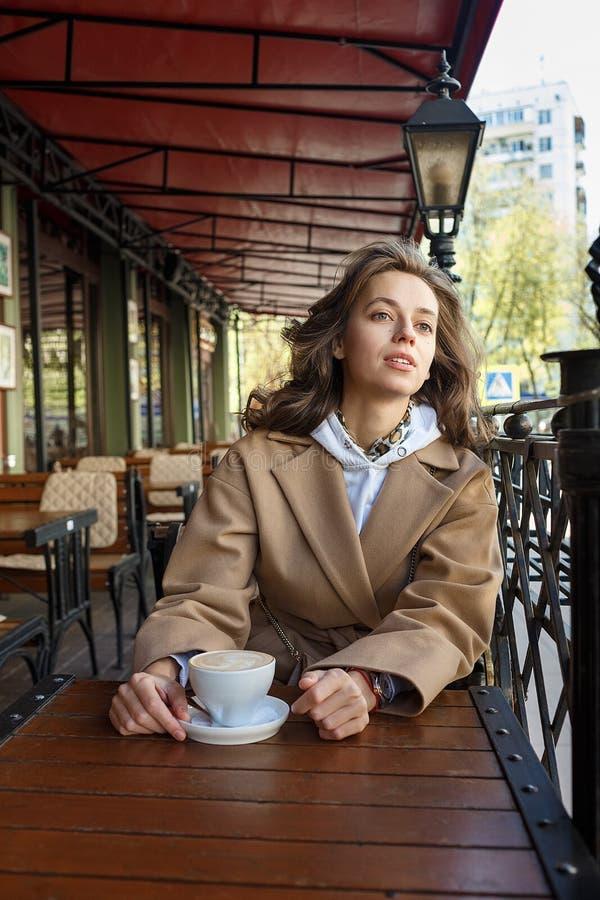 Straatportret van jonge vrouw die beige laag het drinken koffie op koffieveranda dragen met dromerige en nadenkende starende blik royalty-vrije stock foto