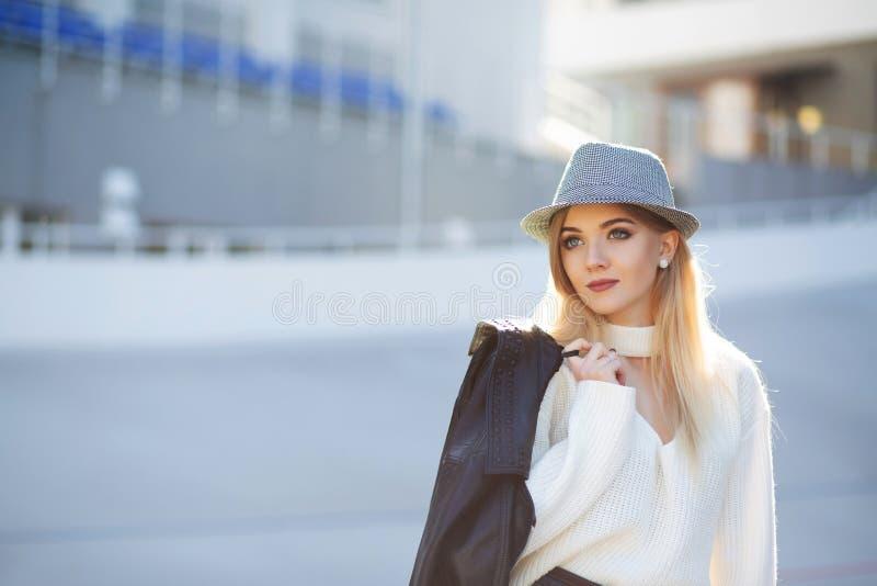 Straatportret van luxueus blonde model dragende hoed en sweate stock afbeelding