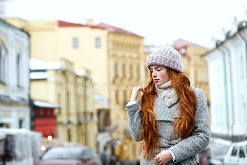 Straatportret van mooi roodharigemeisje met lang haar die wa dragen royalty-vrije stock afbeelding