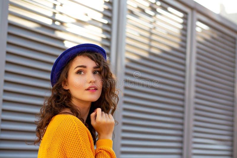 Straatportret van ontzagwekkend model die het blauwe hoed stellen met su dragen royalty-vrije stock afbeeldingen