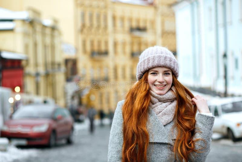 Straatportret van positief roodharigemodel met het lange haar dragen stock foto's