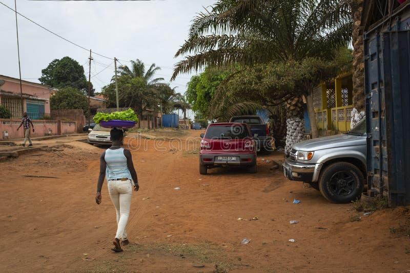 Straatscène in de stad van Bissau met een vrouw die een dienblad met groenten op haar hoofd, in Guinea-Bissau dragen stock foto