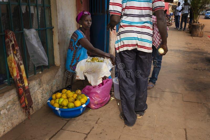 Straatscène in de stad van Bissau met een vrouwen verkopende sinaasappelen, in Guinea-Bissau, West-Afrika royalty-vrije stock afbeeldingen