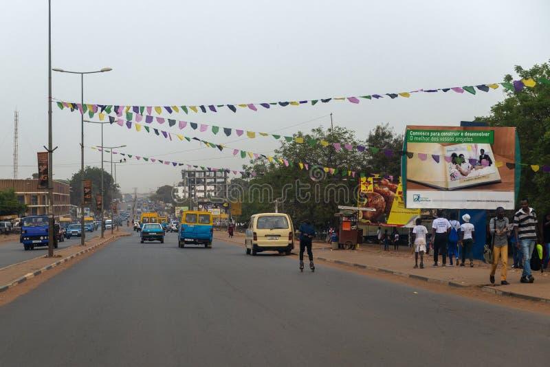 Straatscène in de stad van Bissau met mensen die langs een weg, in Guinea-Bissau, West-Afrika lopen stock foto