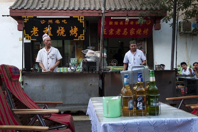 Straatscène in de stad van Dunhuang, met twee kooktoestellen in een voedselbox, in China stock fotografie