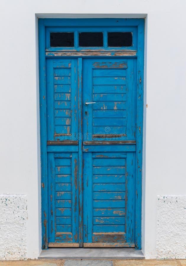 Straatscène en blauwe houten ingang, op Egeïsch Eiland Tinos, Griekenland stock afbeeldingen