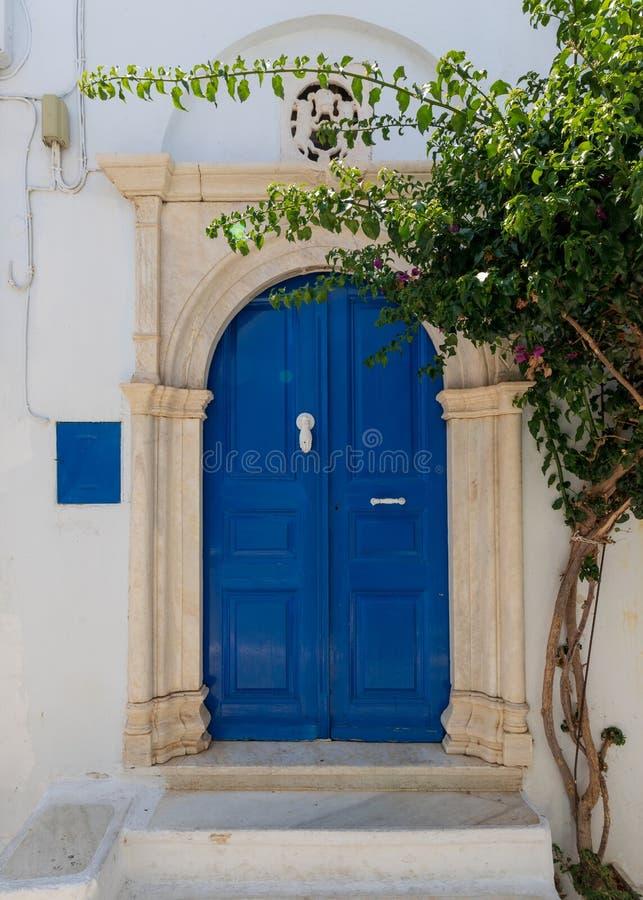 Straatscène en blauwe houten ingang op Egeïsch Eiland Tinos, Griekenland stock fotografie