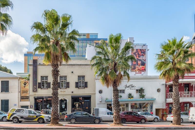 Straatscène, met ondernemingen, voertuigen, palmen, in Kaapslepen stock afbeeldingen