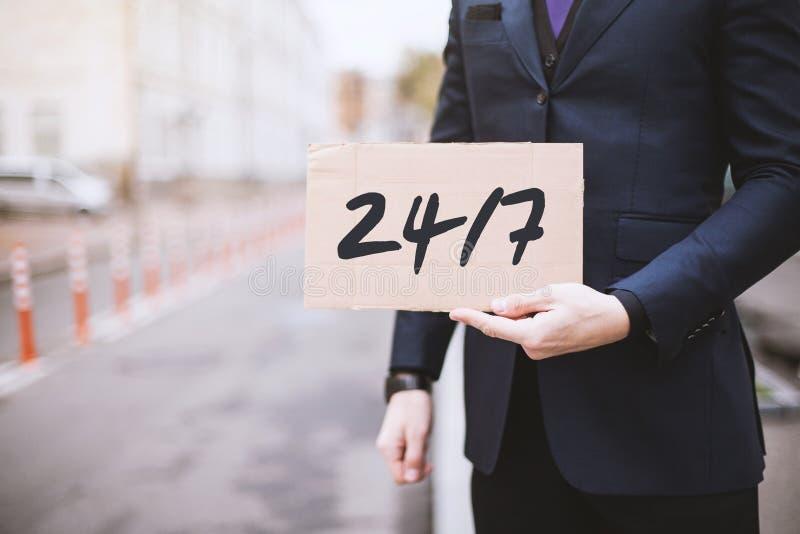 Straatstad, een mens die een teken in zijn handen met de inschrijving houden stock foto