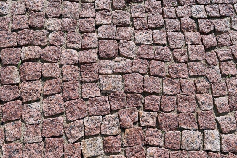 Straatsteen van vierkante granietstenen wordt opgemaakt van bruine kleur die stock fotografie