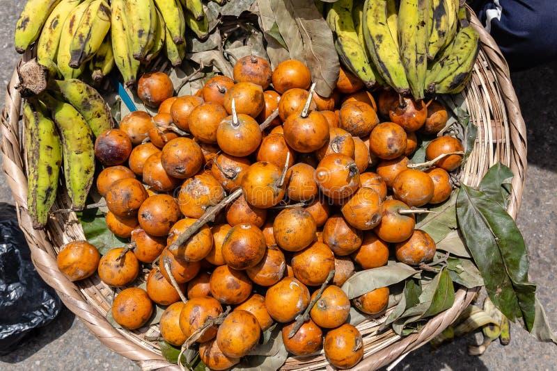 Straatvoedsel in Lagos Nigeria; de banaan en Agbalumo of Afrikaan spelen appel in een mand door de kant van de weg mee stock foto