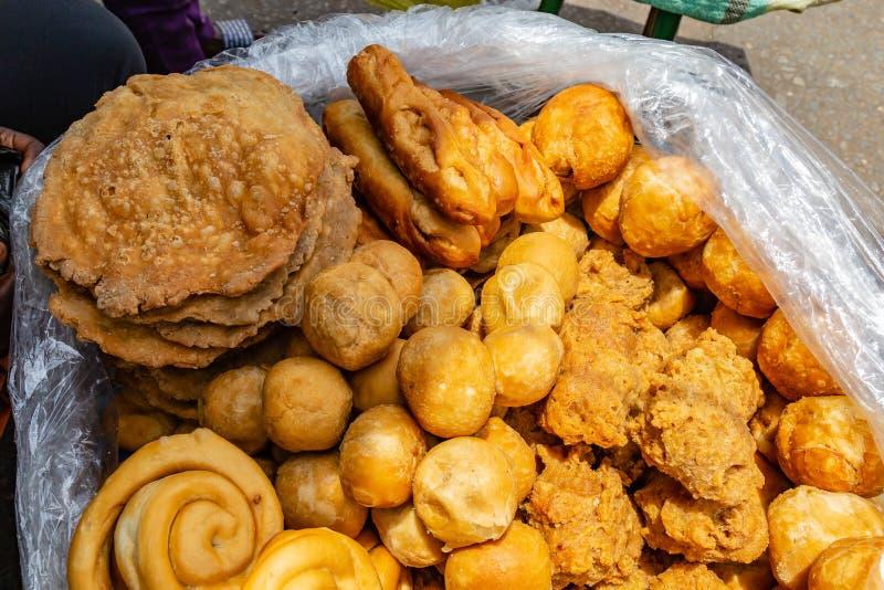 Straatvoedsel in Lagos Nigeria; diverse types van gebakjes en desserts stock afbeeldingen