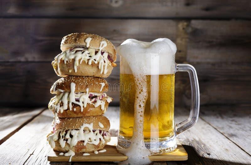 Straatvoedsel licht bier, reusachtige hamburger, snel rundvleespasteitje, maaltijd, snack, bar, ongezonde close-up, rustieke stij stock foto