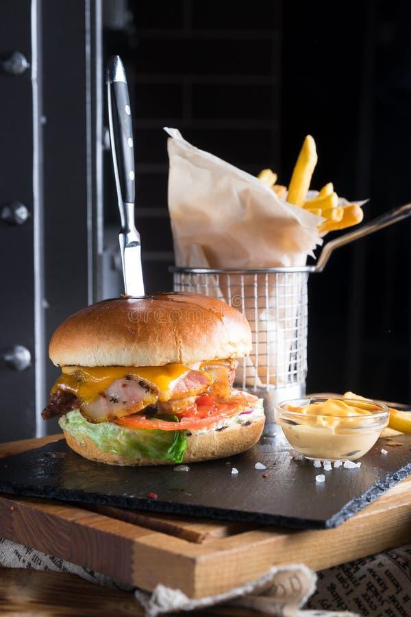 Straatvoedsel, snel voedsel, ongezonde kost Eigengemaakte sappige hamburger met rundvlees, kaas en bacon met frieten op donker en stock afbeelding