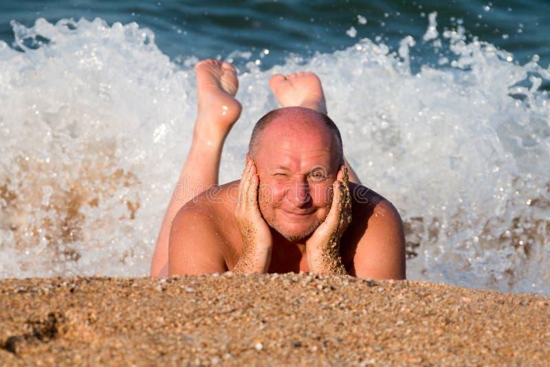 strabismes pluss âgé d'homme du soleil se trouvant sur le sable dans la mousse de mer et se dorant dans les vagues image stock