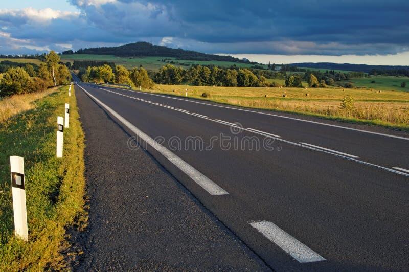 Strada asfaltata attraverso i campi verso l'orizzonte fotografia stock libera da diritti