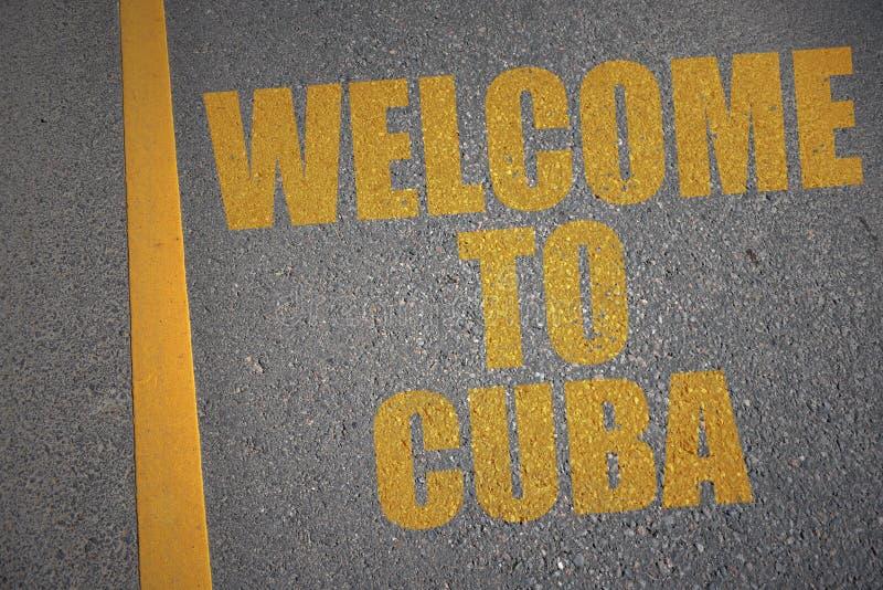 strada asfaltata con il benvenuto del testo in Cuba vicino alla linea gialla royalty illustrazione gratis