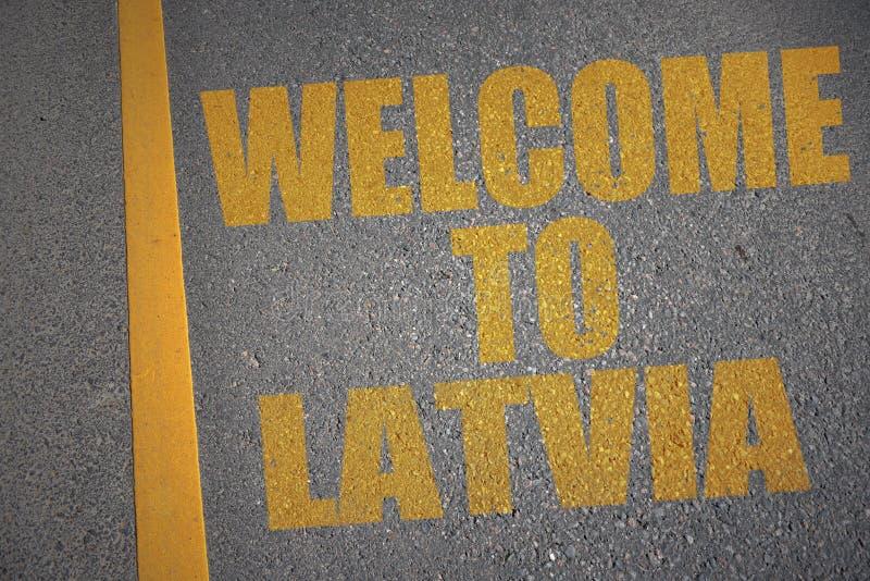 strada asfaltata con il benvenuto del testo in Lettonia vicino alla linea gialla illustrazione di stock