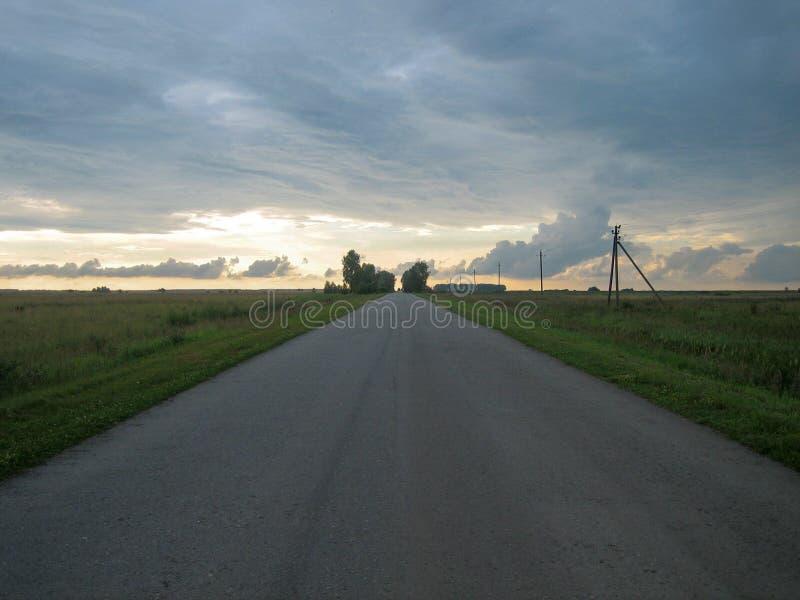 Strada asfaltata diritta liscia nella campagna sotto il cielo con le nuvole al tramonto fotografia stock libera da diritti