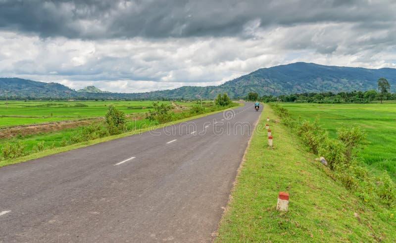 Strada asfaltata, fra i campi, con la gente che guida un ciclomotore verso le montagne fotografia stock libera da diritti