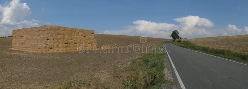 Strada asfaltata fra il campo di agricoltura e un mucchio di fieno con la nuvola di tempesta in un fondo fotografie stock libere da diritti