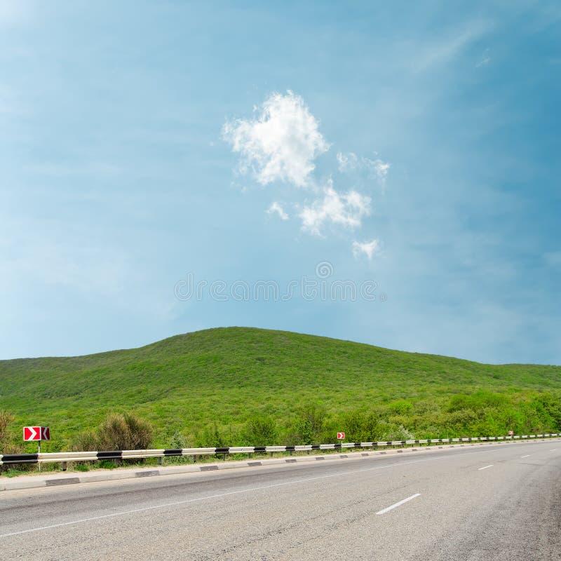 Strada asfaltata in montagna sotto le nuvole leggere immagine stock
