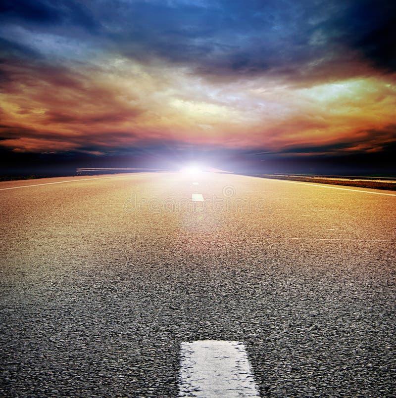 Strada asfaltata nel campo sopra il cielo tempestoso fotografie stock libere da diritti