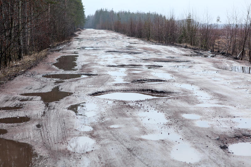 Strada asfaltata rotta in legno con i fori e le pozze fotografia stock
