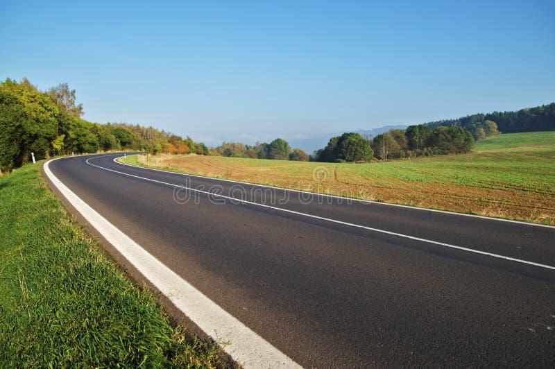 Strada asfaltata vuota in campagna, curvatura della strada immagini stock