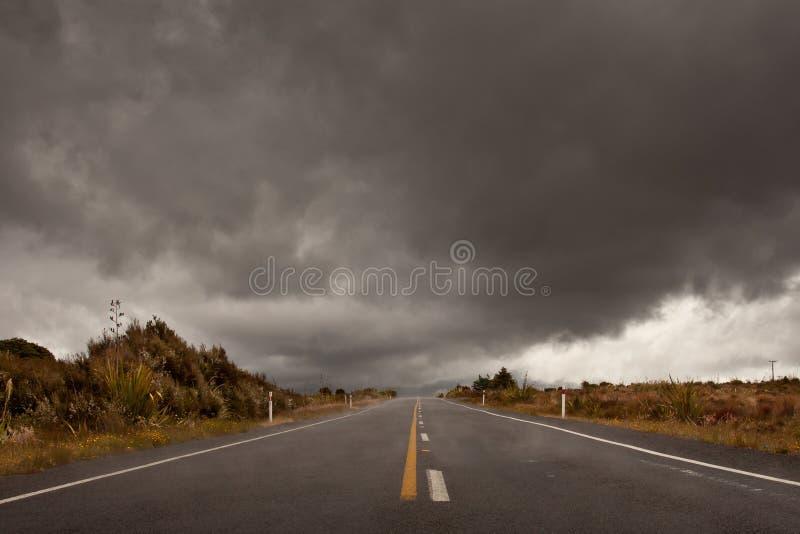 Strada bagnata che piombo in un cielo nuvoloso della tempesta immagini stock libere da diritti