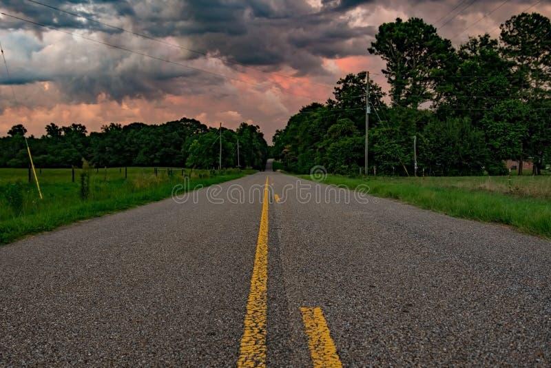Strada bassa di POV che conduce nelle nuvole variopinte fotografia stock libera da diritti