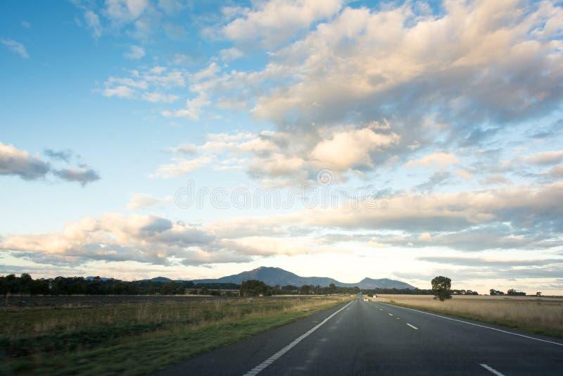 Strada campestre che conduce verso le montagne con il cielo nuvoloso blu immagini stock libere da diritti