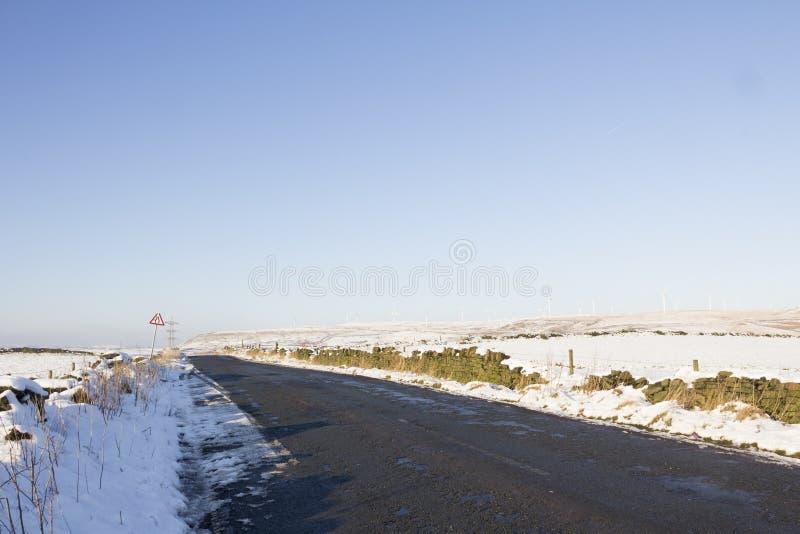 Strada campestre della regione montana in neve con il parco eolico immagini stock