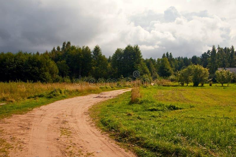 Strada campestre a distanza dopo la pioggia immagine stock