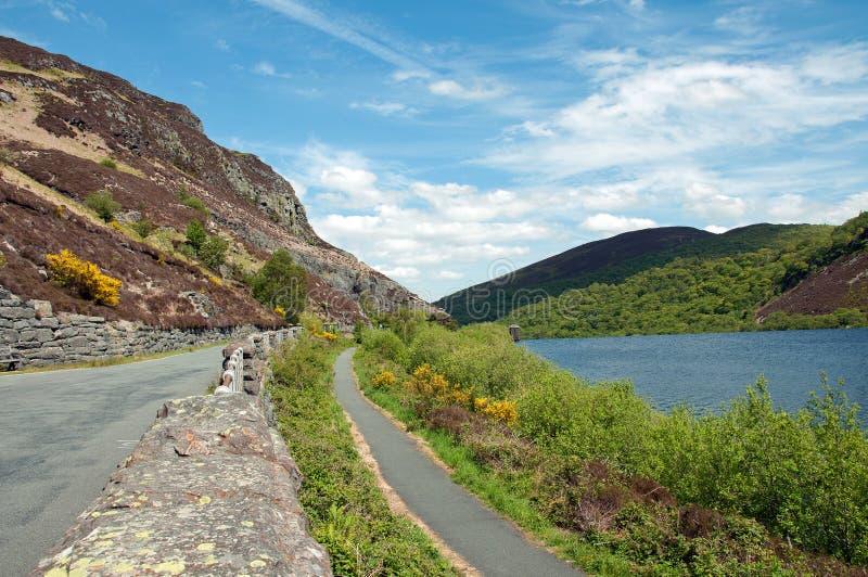 Strada campestre lungo la riva del lago della valle di slancio nell'estate britannica fotografia stock