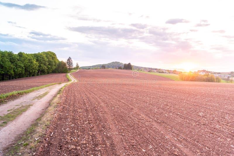 Strada campestre nel paesaggio agricolo rurale Campi rossi del suolo intorno a Nova Paka, repubblica Ceca fotografia stock