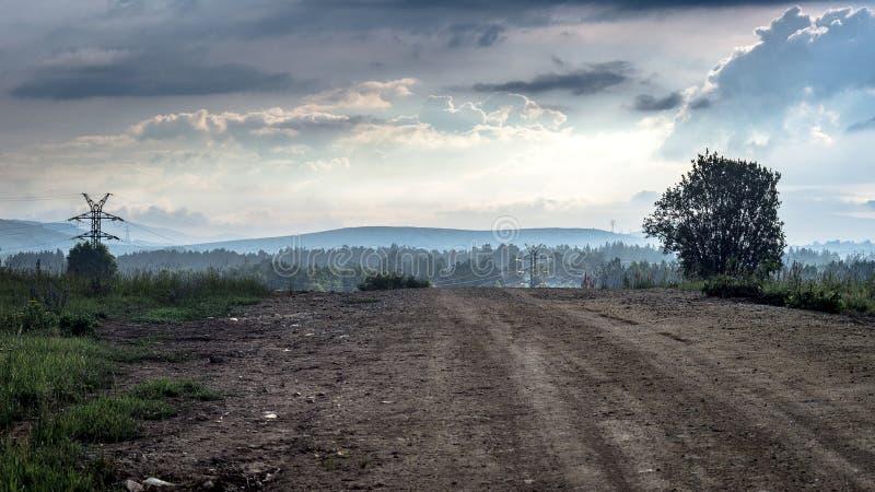 Strada campestre rurale della montagna alla mattina nebbiosa di estate con le nuvole e le linee elettriche drammatiche immagine stock