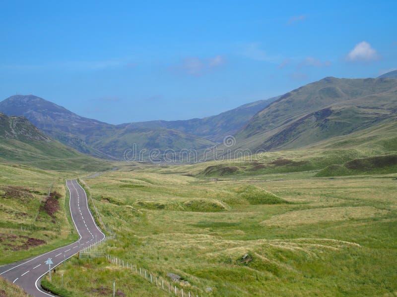 Strada campestre vuota attraverso la brughiera di bellezza in Scozia fotografia stock