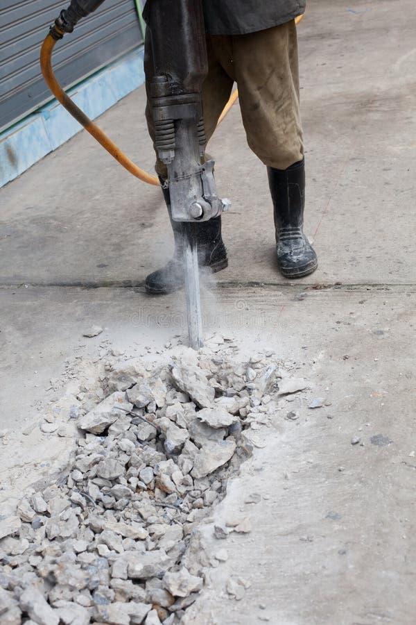 Strada cementata del cemento di perforazione dell'uomo dell'operaio immagine stock