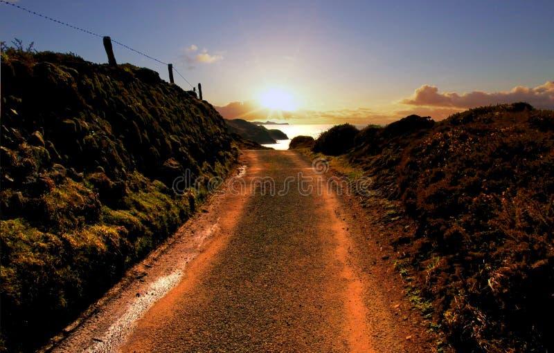 Strada che conduce al tramonto sopra Pembroke Coast immagini stock libere da diritti