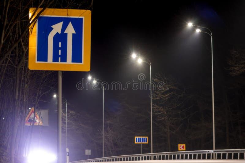 Strada che restringe segno, illuminazione di via, contributi ai soffitti con le lampade principali concetto di modernizzazione e  immagini stock libere da diritti